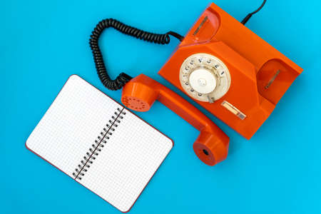 Vintage orange telephone and blank notebook on blue background, top view, pick up the phone