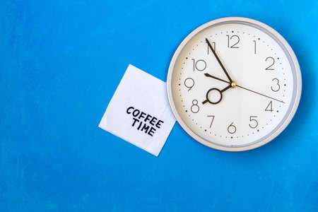 Wall clock with COFFEE TIME note on napkin