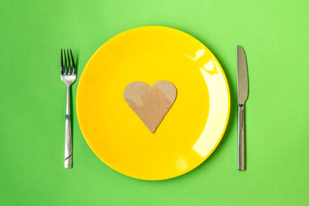 Plate with paper heart and cutlery on green background, flat lay. Healthy diet concept Stock Photo
