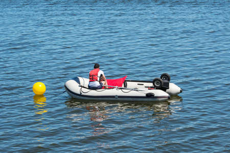 Rettungsschwimmer in einem aufblasbaren Rettungsboot, das im See patrouilliert. Ansicht von hinten. Standard-Bild