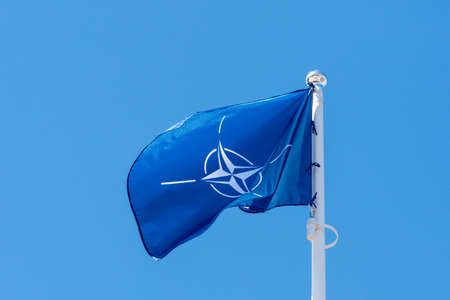 NATO flag waving in the wind against clear sky background