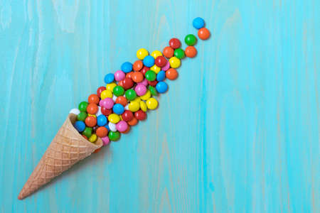 Waffle horn with colored candy on a blue wood background. Top view, copy-space.