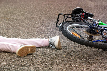 Bicycle accident concept. Girl fallen off her bicycle outdoors.