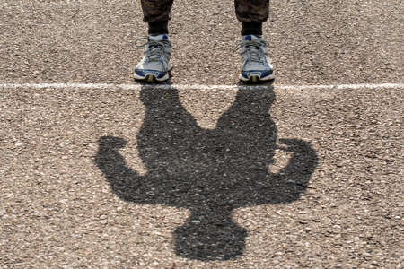 Shadow of man on a stadium running path. Sport concept Stock Photo