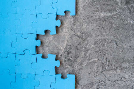 Unfinished blue jigsaw puzzle pieces on stone background. Copy-space