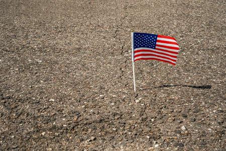 American flag in asphalt road crack