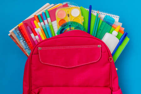 Back to school concept. Backpack with school supplies on the blue background. Stockfoto