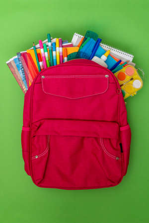 Back to school concept. Backpack with school supplies on the green background.