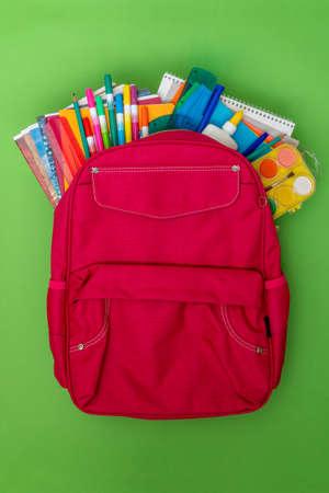 Concepto de regreso a la escuela. Mochila con útiles escolares en el fondo verde.