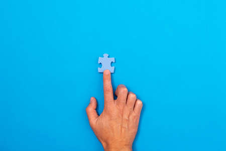 Concept of business. Hand pointing at pieces of puzzle ower a blue background