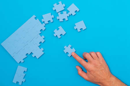 Concept of business. Hand pointing at pieces of puzzles and collecting them together Reklamní fotografie