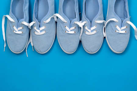 Row of soft blue color canvas shoes on blue background