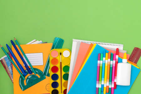 School supplies, stationery accessories on a green background. Flat lay, copy-space