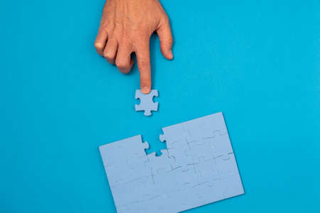 Concept of business, finding solution. Businessman solving puzzle on blue background.
