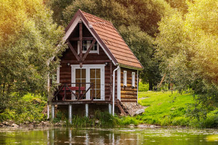 Small wooden house near the lake, sunny summer day