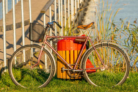 Old bicycle standing beside bridge of small lake