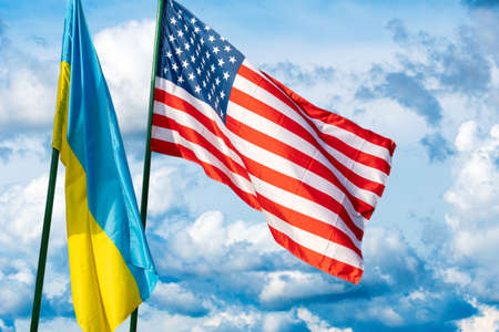 Flags of the USA and Ukraine against the background of the cloudy sky