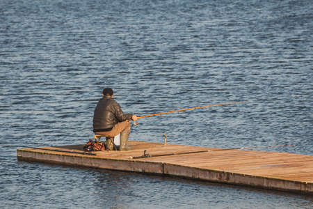 Unrecognizable rear view of  senior man fishing on the lake