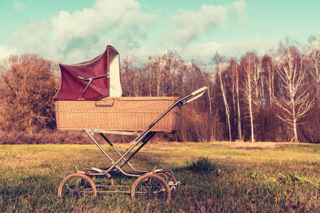 Retro style stroller baby carriage outdoors with autumn landscape Stock Photo