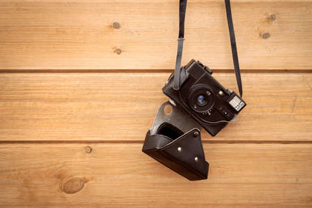 Old 35mm camera hanging on wood wall. Copy-space.