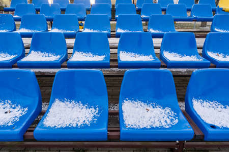 Stadium seats in the snow in winter. Snow-covered blue plastic seats at the small stadium in winter. Snowfall interferes with sports. Uncleaned stadium.