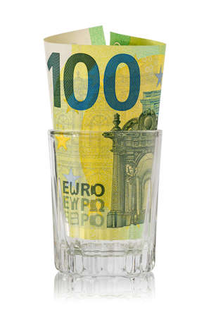 Glass for alcohol with one hundred Euro inside. Money lost through alcohol addiction