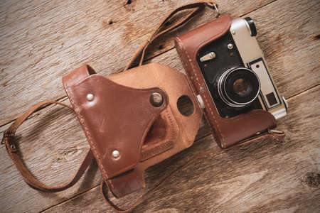Old film camera lying on the wooden background. Top view.