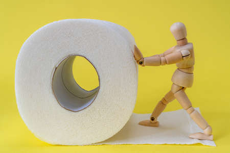 Wooden man pushes a roll of toilet paper. Concept of the problem with digestion. Foto de archivo