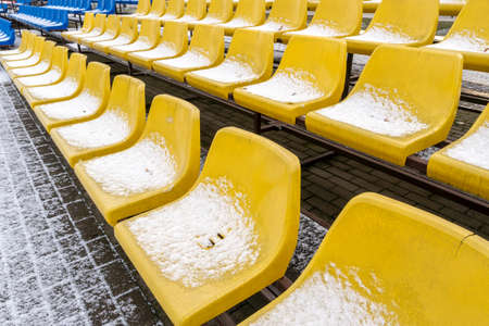 Stadium seats in the snow in winter. Snow-covered yellow plastic seats at the stadium in winter. Snowfall interferes with sports. Uncleaned stadium.