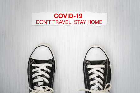 "Shoes and note with phrase ""Don't travel, stay home"".Stop coronavirus. Self isolation. Home quarantine from Covid-19. Recommendation to prevent spreading Coronavirus, Covid 19 lockdown."