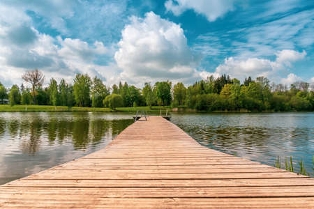 Mole (pier) on the lake. Wooden bridge in forest in spring time with calm lake. Lake for fishing and recreation with pier.