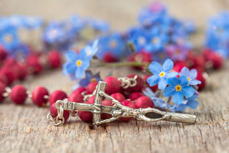 Rosary and blue forget-me-nots flowers. Religion concept. Standard-Bild