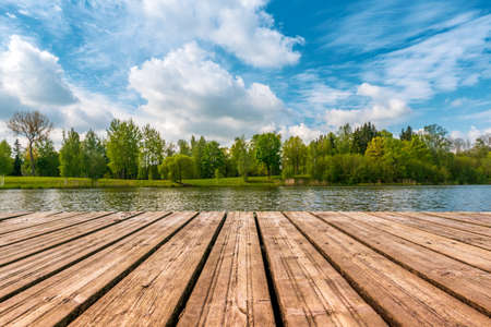 Idyllic view of the wooden pier in the lake with forest scenery background. Reklamní fotografie