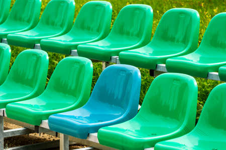 A single blue chair in a multitude of green ones. Different from the others.