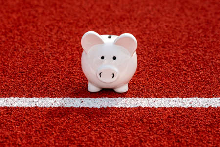 Piggy bank on starting line in the stadium. Concept sport funds and finances