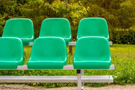 Empty sports stands with green seats on an summer day.