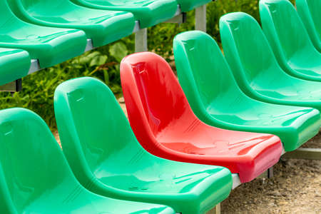 One red seat among different color (green) seats in a stadium (UNIQUE / CONFIDENCE CONCEPT)