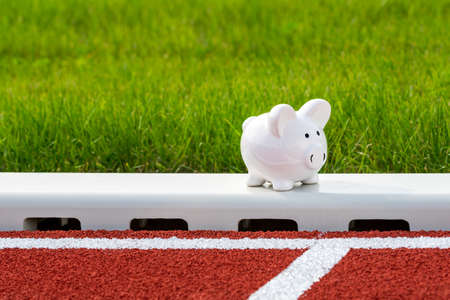 Piggy bank on the running track in the stadium.  Concept of sport fund. Money and sport. 版權商用圖片