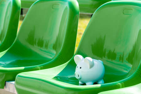 Piggy bank on the green chairs of sports stadium. Sports and money.
