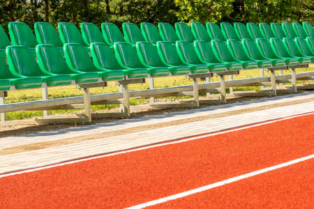 Running track and plastic chairs in a row on sports stadium