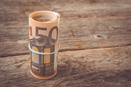 Roll of fifty euro banknotes on the old wooden background