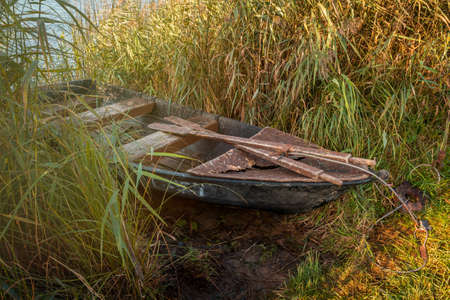 An old abandoned wooden boat left near the lake, used by local people for fishing, boat in poor condition