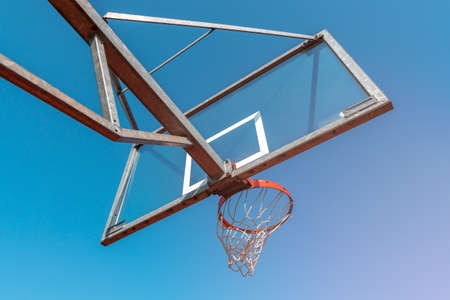 Bottom view of basketball hoop and clear blue sky. The concept of sports and a healthy lifestyle