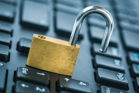 Computer security concept. Unlocked padlock on laptop keyboard. Open security lock on computer keyboard - computer security breach concept.