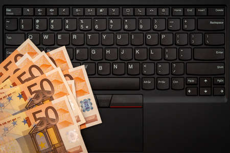Money cash banknote on laptop keyboard, digital money and e-commerce concept. Top view.