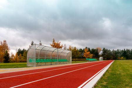 Green chair for spare team near running track in the stadium