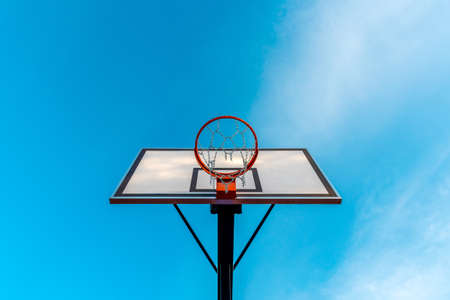 Basketball hoop against clear sky background. View from bottom.