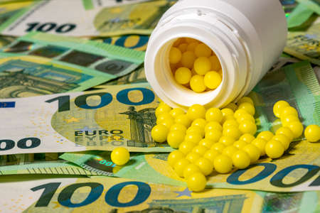 Pills of vitamin C spilled on Euro currency background