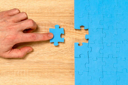 Hand put the last piece of jigsaw puzzle to complete the mission. Must important part, finishing complicated project, solution.