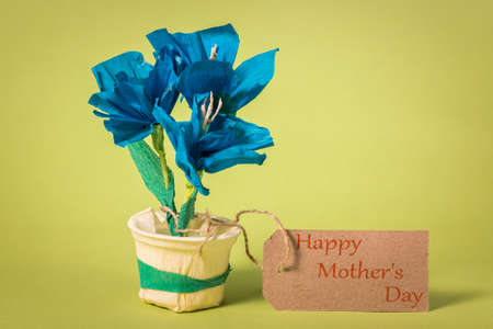 "Children's handicraft paper flowers, made of colorful paper. Greetings for Mom on Mother's Day with the inscription ""Happy mothers day""."